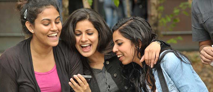 Students looking at phone screen.