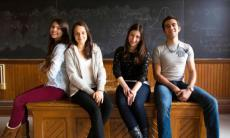 Four students sitting on a desk