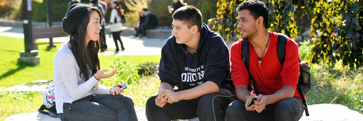 Three students sitting outside