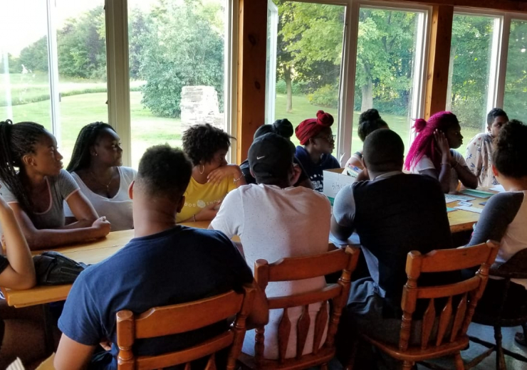 Students gathered around a table having a discussion